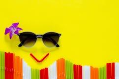 Солнечные очки и солома установили как счастливая сторона выражения с цветком орхидеи на красочных соломах и желтом цвете стоковое изображение