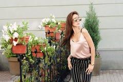 Солнечные очки красивой молодой женщины нося, в деревянной рамке Модель носит стильные одежды, бежевый knitwear и черноту стоковая фотография rf