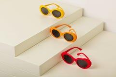 Солнечные очки красных, оранжевых и желтых цветов на белом backgroun Стоковое Изображение