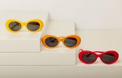 Солнечные очки красных, оранжевых и желтых цветов на белом backgroun Стоковые Изображения