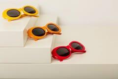Солнечные очки красных, оранжевых и желтых цветов на белом backgroun Стоковые Фотографии RF