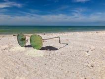 Солнечные очки лежа на каникулах убежища песчаного пляжа стоковые изображения rf
