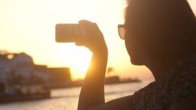 Солнечные очки милой девушки нося принимая фото против изумительного захода солнца во время круиза моря с влияниями пирофакела об стоковое изображение