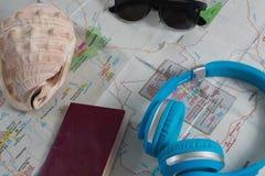 Солнечные очки, наушники, пасспорт и seashell на карте Стоковые Фото