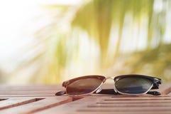 Солнечные очки на деревянной таблице на пляже с кокосовой пальмой Стоковые Фотографии RF