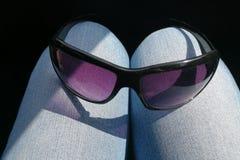 Солнечные очки на коленях стоковое изображение