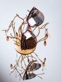 Солнечные очки с коричневыми стеклами на золотом постаменте на предпосылке зеркала стоковое фото