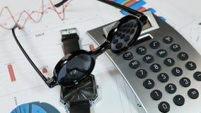 Солнечные очки, часы и калькулятор лежат на предпосылке диаграмм Идеи и концепции дела Стоковые Изображения