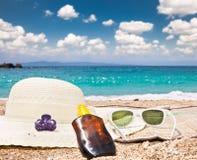 Солнечные очки, sunsunhat, suncream на пляже Стоковые Фото