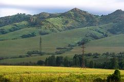 Солнечные самые интересные на наклонах зеленых холмов, восход солнца в горах, линии электропередач и дорога в переднем плане Стоковое Изображение