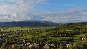 Солнечный летний день и небольшая деревня в montain в голубом небе видеоматериал