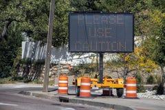Солнечный мобильный знак с оранжевыми конусами сидя на тротуаре кроме дороги говоря пожалуйста предосторежение пользы - выборочны стоковые изображения rf