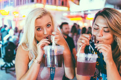 СОЛНЕЧНЫЙ ПЛЯЖ, БОЛГАРИЯ, 29-ОЕ АВГУСТА 2015: Девушки партии на улице цветка выпивают коктеили Стоковое Фото