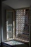Солнечный свет через богато украшенный гриль окна металла стоковое фото
