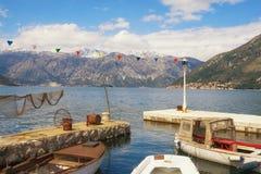 Солнечный среднеземноморской ландшафт с снег-покрытыми горами и рыбацкими лодками в малой гавани Черногория, залив Kotor Стоковые Изображения RF