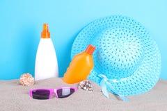 Солнцезащитный крем с аксессуарами лета в песке моря стоковые фотографии rf
