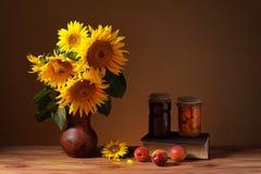 Солнцецвет в вазе, плодоовощах и книгах стоковые изображения rf