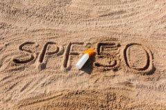 Солнце защищает фактор 50 Слово SPF 50 написанное на песке и белой бутылке со сливк suntan Предпосылка концепции заботы кожи стоковое изображение rf