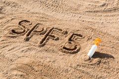 Солнце защищает фактор 5 Слово SPF 5 написанное на песке и белой бутылке со сливк suntan Предпосылка концепции заботы кожи стоковая фотография rf