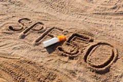 Солнце защищает фактор 50 Слово SPF 50 написанное на песке и белой бутылке со сливк suntan Предпосылка концепции заботы кожи стоковые фото