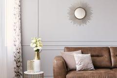 Солнце любит форменное зеркало над софой кожи с подушками в серой элегантной живущей комнате стоковое фото rf
