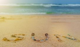 Солнце написанное с различными раковинами на песке с предпосылкой океана стоковые изображения