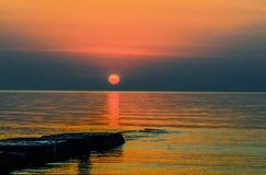 Солнце оранжевого красного цвета поднимает над золотыми волнами океана Стоковая Фотография