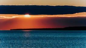 Солнце промежутка времени устанавливает за облаком - красно-розовым заходом солнца на море или большом озере сток-видео