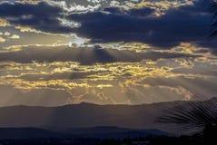 Солнце пряча за некоторой плотной облачностью стоковое изображение