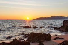 Солнце прячет край пляжа стоковое фото
