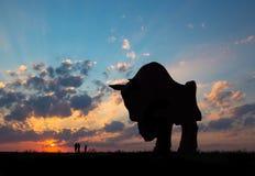 Солнце рассвета захода солнца излучает над семьей силуэта скульптуры бизона статуи поля неба города идя около солнца стоковая фотография