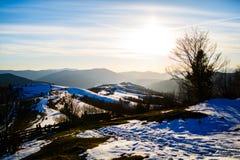 Солнце светя над горами Снег плавя на наклонах холма стоковые фотографии rf