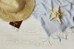 Соломенная шляпа женщин, красные паспорт и билет на самолет, голубое tippet и морские звёзды на белой деревянной предпосылке - ко стоковая фотография rf