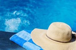 Соломенная шляпа и голубое полотенце около бассейна Стоковое Изображение