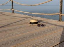 Соломенная шляпа и солнечные очки на досках деревянной старой пристани стоковая фотография