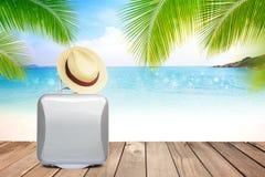 Соломенная шляпа и чемодан Брайна на деревянном столе с запачканными морем, голубым небом и предпосылкой пальмы с космосом экземп Стоковое Изображение RF