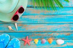 Соломенная шляпа, солнечные очки, тапочка, морские звёзды и shellsn на деревянной планке в голубом море красят предпосылку цвета Стоковые Изображения RF