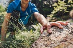 Сольный человек взбираясь утес в лесе стоковое фото rf