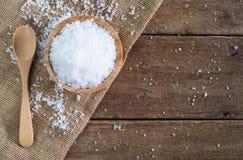 Соль белого моря в деревянном шаре с деревянной ложкой на ткани мешка реднины на коричневом деревянном столе Стоковое фото RF