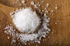 Соль моря в деревянной ложке над древесиной Стоковые Изображения RF