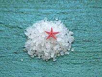 Соль моря с морскими звёздами на деревянной предпосылке Стоковые Фото