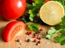 Соль перца петрушки лимона томатов свежих овощей грубое на разделочной доске Стоковые Изображения RF