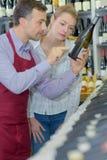 Сомелье и женская рудоразборка клиента разливают вино по бутылкам в магазине Стоковое фото RF