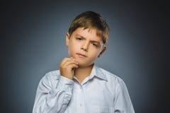 Сомнение, выражение и концепция людей - мальчик думая над серой предпосылкой Стоковое Фото