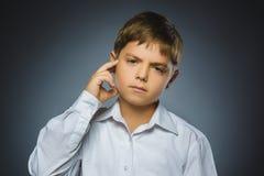 Сомнение, выражение и концепция людей - мальчик думая над серой предпосылкой Стоковые Изображения RF