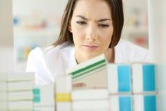 Сомнительный аптекарь проверяя медицину Стоковая Фотография RF