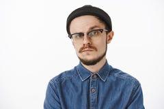 Сомнительный и неуверенный выглядящий серьезн bossy мужской предприниматель в черной рубашке и стеклах beanie поднимая одну бровь стоковые фотографии rf