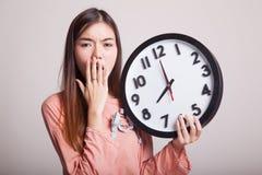Сонная молодая азиатская женщина с часами в утре стоковое фото