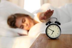 Сонная молодая женщина протягивая руку к звеня повороту сигнала тревоги охотно готовому оно  Предыдущее бодрствование вверх, не п стоковое фото rf