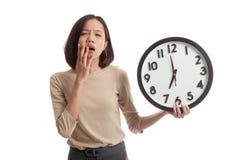 Сонная молодая азиатская бизнес-леди с часами в утре Стоковое Изображение